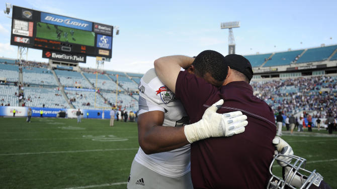 Mississippi State defensive lineman Devin Jones (60) hugs an assistant coach after losing 34-20 to Northwestern in the Gator Bowl NCAA college football game, Tuesday, Jan. 1, 2013 in Jacksonville, Fla.  (AP Photo/Stephen Morton)