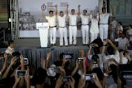 Singapore's Prime Minister Lee Hsien Loong, third from left on stage leads his colleagues of the ruling People's Action Party as they celebrate a win in their constituency in Singapore, Saturday, Sept. 12, 2015. The party that has ruled Singapore since it became a country a half-century ago appeared poised to stay in power for five more years as the city-state's citizens voted Friday in a compulsory election. (AP Photo/Ng Han Guan)
