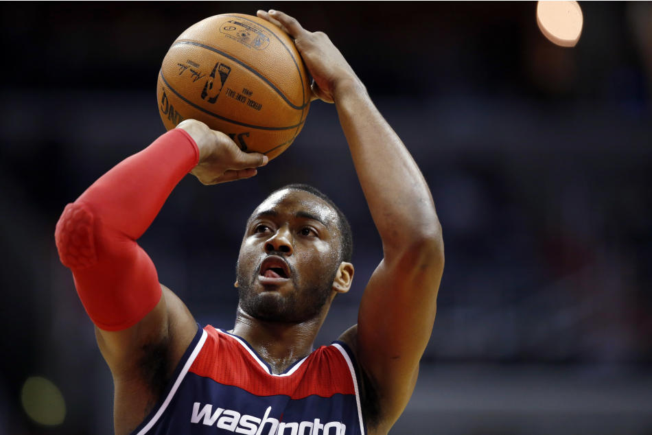 FILE - In this March 25, 2015, file photo, Washington Wizards guard John Wall shoots a free throw during an NBA basketball game against the Indiana Pacers in Washington. Police say Wall was kicked off