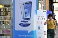 "A woman walks past a signboard for the Samsung Galaxy S3 at a mobile phone shop in Seoul. South Korea's Samsung Electronics vowed on Tuesday to take ""all necessary measures"" to keep its products on US store shelves, in response to Apple's request for a ban on sales of some smartphones"