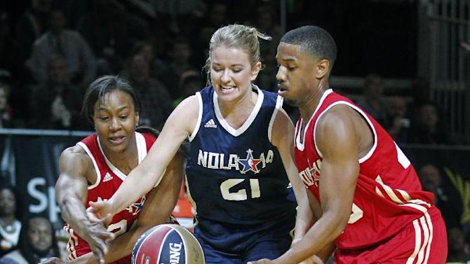 East's Kristen Ledlow (21) reaches for a loose ball between West's Michael B. Jordon (45), right, and Tamika Catchings (24), left, in the second half as they participate in the NBA All-Star Celebrity basketball game in New Orleans, Friday, Feb. 14, 2014. East won 60-56