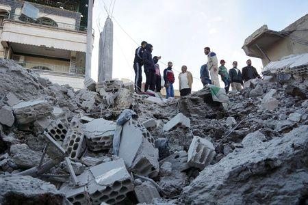 Residents inspect a damaged site from what activists said were airstrikes carried out by the Russian air force in Nawa city, Deraa, Syria