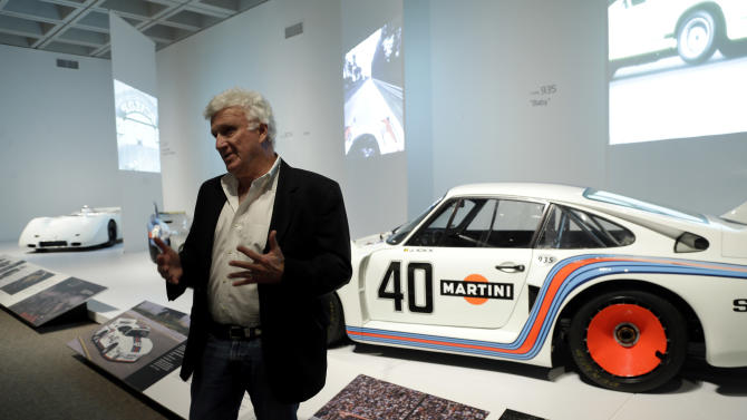 In this photo taken Wednesday, Oct. 9, 2013 Porsche By Design Seducing Speed exhibit curator Ken Gross is seen with some of the Porsche cars on display at the North Carolina Museum of Art in Raleigh, N.C. (AP Photo/Gerry Broome)