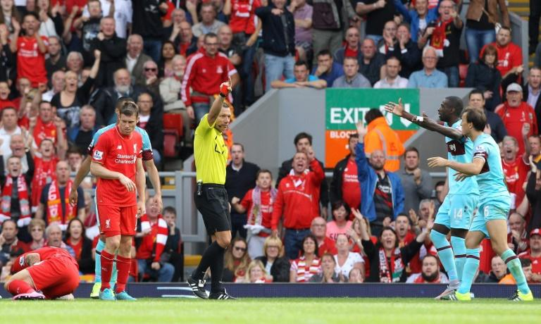 West Ham United's Mark Noble (R) receives a red card from referee Kevin Friend (3rd R) for a challenge on Liverpool's Danny Ings (Below L) during an English Premier League football match at An