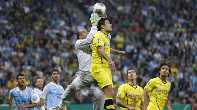 Munich's Garbor Kiraly, left, and Dortmund's Sokratis of Greece challenge for the ball during the German soccer cup second round match between TSV 1860 Munich and Borussia Dortmund, in Munich, southern Germany, Tuesday, Sept. 24, 2013