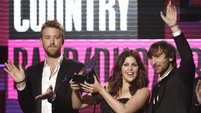 FILE - In this Nov. 20, 2011, file photo Lady Antebellum musical group members from left, Charles Kelley, Hillary Scott and Dave Haywood, accept the award for country band, duo or group at the 39th Annual American Music Awards on in Los Angeles. Students from the wrecked school awaited word Tuesday, March 20, 2012, about whether on online campaign supported by other schools in their state and beyond will land them a prom-night performance by Grammy-winning country trio Lady Antebellum.  (AP Photo/Matt Sayles, File)