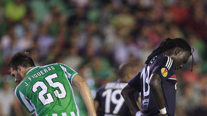 Olympique Lyon's Gomis reacts next to Real Betis' Figueras during Europa League soccer match in Seville