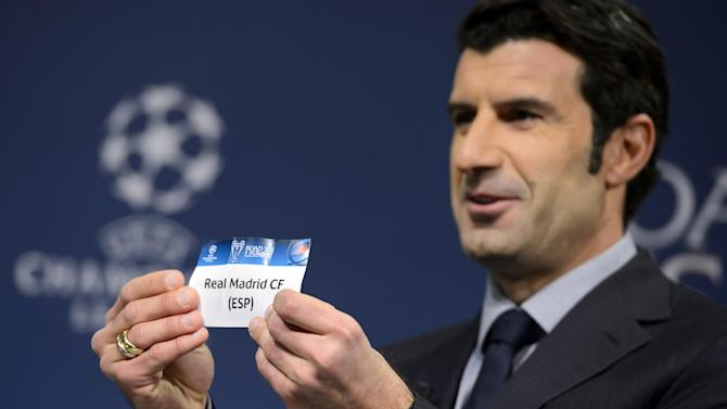 Former Portugal soccer player and Champions League Lisbon final ambassador Luis Figo shows a ticket with Spain's soccer team Real Madrid during the draw of the round of 16 games of UEFA Champions League 2013/14 at the UEFA Headquarters in Nyon, Switzerland, Monday, Dec. 16, 2013