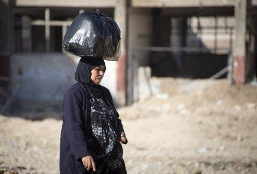 A woman carries foodstuffs on her head in the Aleppo neighbourood of Tariq al-Bab on December 8, 2012. Residents of Aleppo have suffered through months of brutal urban warfare and now face a humanitarian crisis with a lack of food and fuel as the Syrian winter sets in
