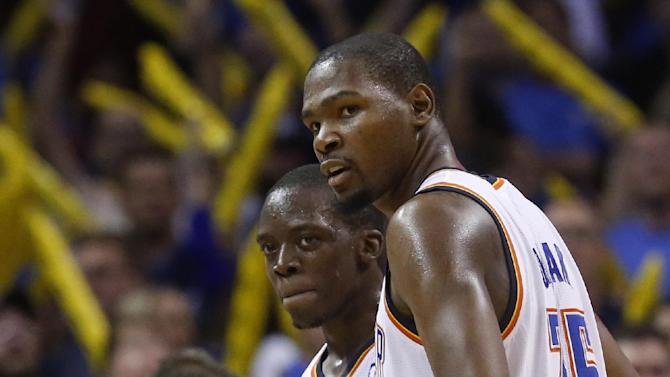 Oklahoma City Thunder guard Reggie Jackson (15) and forward Kevin Durant (35) looks towards the Washington Wizards bench as they walk off the court following an NBA basketball game in Oklahoma City, Sunday, Nov. 10, 2013. Oklahoma City won 106-105 in overtime