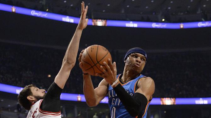 Oklahoma City Thunder guard Russell Westbrook (0) looks pass the ball as Chicago Bulls forward Nikola Mirotic (44) defends him during the first half of an NBA basketball game, Thursday, March 5, 2015 in Chicago.  (AP Photo/David Banks)