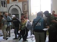 "A Shaam News Network image shows UN observers at a hospital morgue in the central Syrian town of Houla on May 26. UN-Arab envoy Kofi Annan expressed ""horror"" at the Houla massacre of more than 100 people as he began a visit on Monday to the Syrian capital aimed at salvaging his battered peace plan"