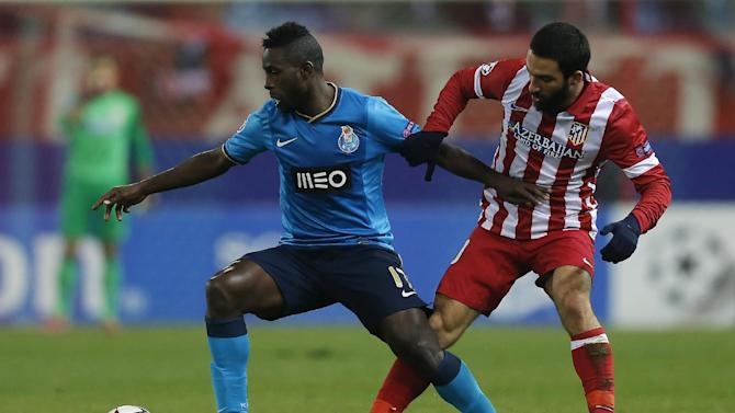 Atletico's Arda Turan, right, in action with Porto's Silvestre Varela, left, during a Champions League Group G soccer match between Atletico Madrid and FC Porto, at the Vicente Calderon stadium in Madrid, Wednesday, Dec. 11, 2013