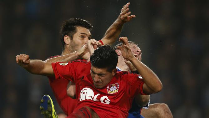 Bayer Leverkusen's Spahic, Can and Arminia Bielefeld's Klos jump for the ball during the second round of their German soccer cup match in Bielefeld
