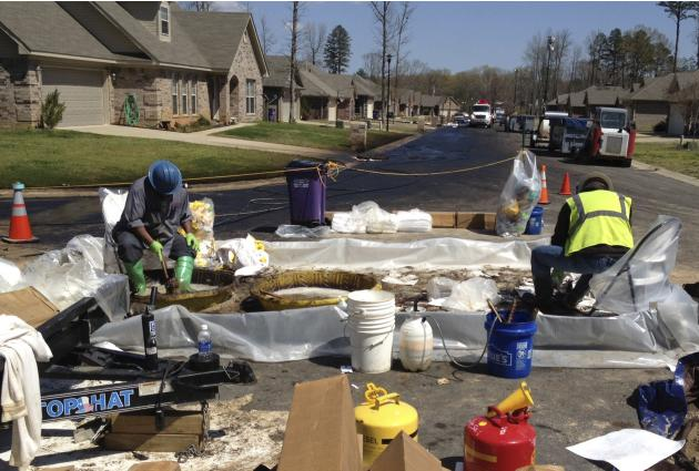 File of workers scrubing crude oil from their boots in the Northwoods subdivision where an ExxonMobil pipeline ruptured in Mayflower