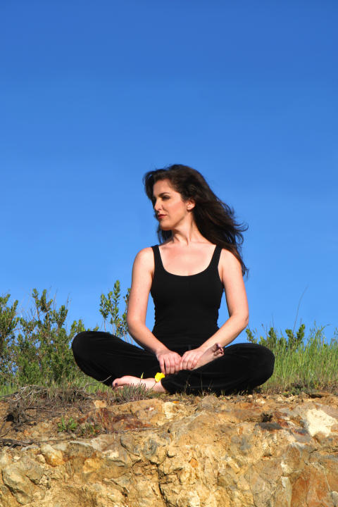 A young woman meditating outdoors