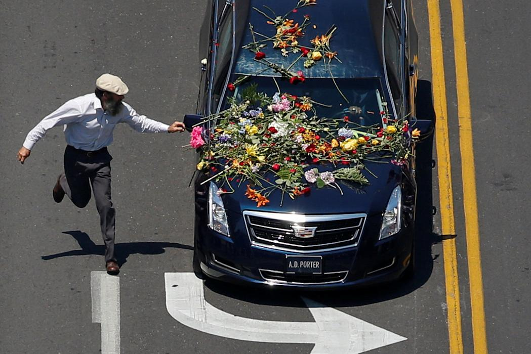Man races to place flowers on hearse carrying body of  Muhammad Ali during funeral procession through Louisville, Kentucky