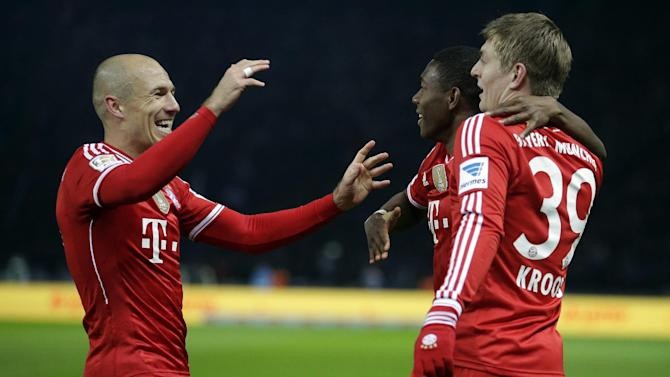 Bayern's Arjen Robben of the Netherlands, left, David Alaba of Austria center, and scorer Toni Kroos, right, celebrate their side's opening goal during  the German Bundesliga soccer match between Hertha BSC Berlin and Bayern Munich in Berlin, Germany, Tuesday, March 25, 2014