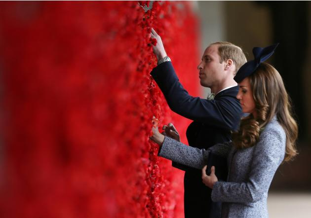 Britain's Prince William and his wife Catherine, Duchess of Cambridge, place poppy flowers into the World War One Wall of Remembrance on ANZAC Day in Canberra