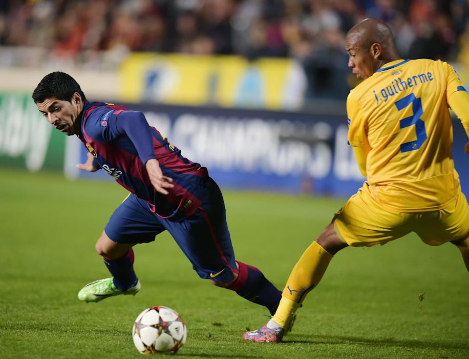 APOEL Nicosia's Guilherme and Barcelona's Suarez fight for the ball during their Champions League soccer match in Nicosia