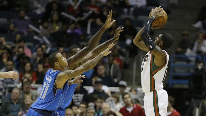 Milwaukee Bucks' O.J. Mayo, right, puts up a shot against Dallas Mavericks' Monta Ellis during the first half of an NBA basketball game Saturday, Nov. 9, 2013, in Milwaukee