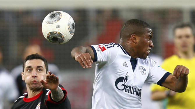 Bayer Leverkusen's Hilbert challenges Schalke 04's Farfan during their German first division Bundesliga soccer match in Leverkusen