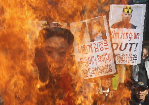 South Korean protesters burn an effigy of North Korean leader Kim Jong Un during an anti-North Korea rally denouncing the North's nuclear test  in Seoul, South Korea, Wednesday, Feb. 13, 2013. A day a