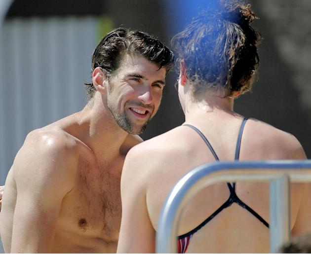 Michael Phelps talks with a fellow swimmer after practice, Wednesday, April 23, 2014, in Mesa, Ariz. Phelps is competing in the Arena Grand Prix at Mesa, as he returns to competitive swimming after a