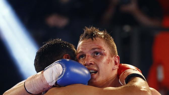 Italy's Di Rocco embraces Denmark's Bruun after winning their European super lightweight boxing title fight in Milan