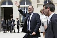 French President Francois Hollande (C) waves to the crowd at the Elysee Palace. Hollande said on Saturday the players who represented France at football should take a leaf out of the book of the young men who don the French army uniform