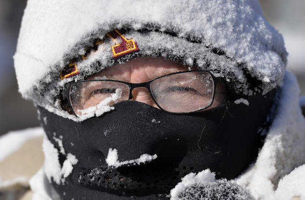 Milissa Preiss peers out from behind snow-covered glasses while clearing her Sartell, Minn., driveway Tuesday, March 3, 2015. A fast-moving storm dumped several inches of snow across the Upper Midwest