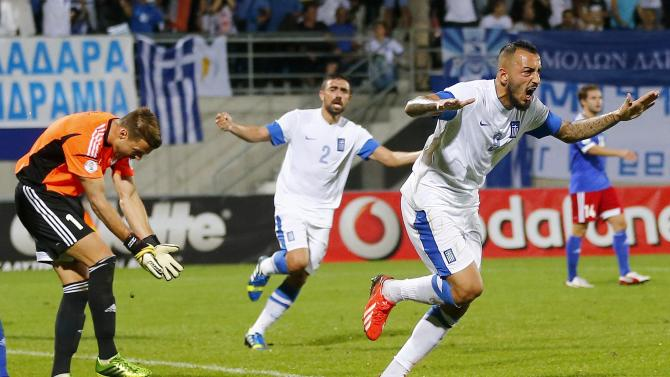 Mitroglou of Greece and his team mate Maniatis celebrate after he scored during their 2014 World Cup Group G qualifying soccer match against Liechtenstein in Vaduz