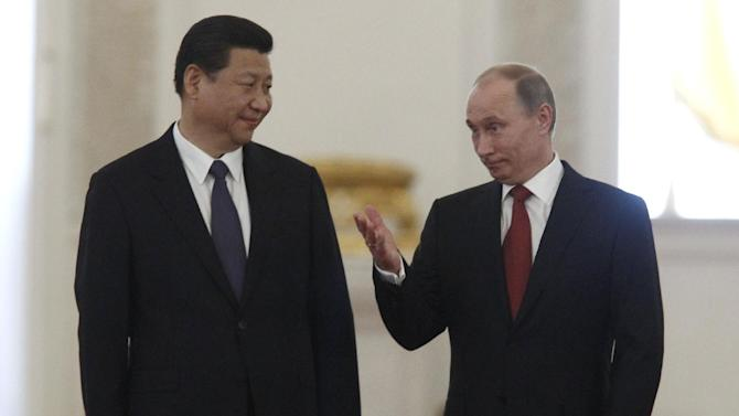 Russian President Vladimir Putin, right, escorts Chinese President Xi Jinping for talks in the Grand Kremlin Palace in Moscow, Russia, Friday, March 22, 2013. Russia is Xi Jinping's first foreign destination as China's president. Xi's talks with Putin on Friday are set to focus on oil and gas as China seeks to secure new energy resources to fuel its growing economy. (AP Photo/Sergei Karpukhin, Pool)
