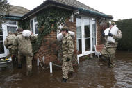 British army soldiers place sandbags at the entrance to a flooded house at Chertsey, England, Wednesday, Feb. 12, 2014. The River Thames has burst its banks after reaching its highest level for many years, flooding riverside towns upstream of London, including Chertsey which is about 30 miles west of central London. Some hundreds of troops have been deployed to assist with flood protection and to get medical assistance to the sick and vulnerable. (AP Photo/Sang Tan)