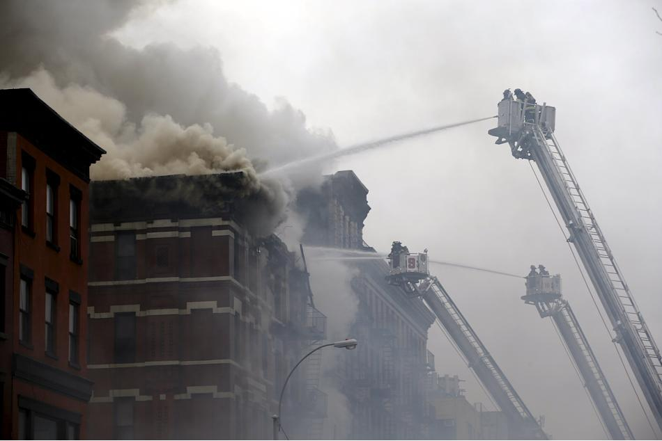 Firefighters battle fire at the site of a residential apartment building in New York City's East Village neighborhood