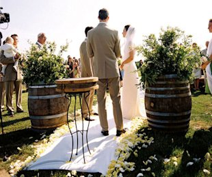 A couple exchanges vows, framed by barrels of lush wildflowers.
