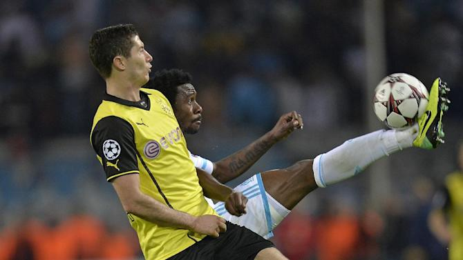 Dortmund's Robert Lewandowski of Poland, left, and Marseille's Nicolas N'Koulou challenge for the ball during the Champions League group F soccer match between Borussia Dortmund and Olympique Marseille in Dortmund, Germany, Tuesday Oct. 1, 2013. Dortmund defeated Marseille with 3-0