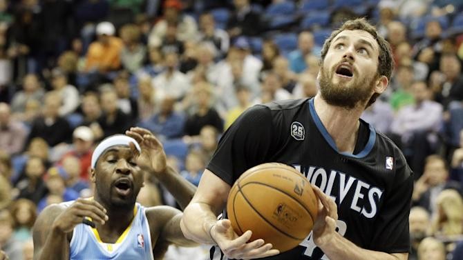 Minnesota Timberwolves' Kevin Love, right, eyes the basket in front of Denver Nuggets's Ty Lawson in the first quarter of an NBA basketball game on Wednesday, Nov. 27, 2013, in Minneapolis