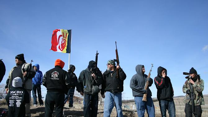 Members of the American Indian Movement stand near the Wounded Knee Massacre Monument, Wednesday, Feb. 27, 2013 in Wounded Knee, S.D. Wednesday marked the 40th anniversary of the start of the 71-day occupation in the village of Wounded Knee on the Pine Ridge Indian Reservation. Hundreds of AIM members and other supporters turned out for a day of ceremonies to commemorate the anniversary of the fatal standoff that drew national attention to the impoverished reservation and the plight of local tribes. (AP Photo/Kristi Eaton)