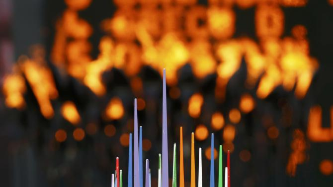Javelins are seen in front of the Olympic flame during the London 2012 Olympic Games at the Olympic Stadium