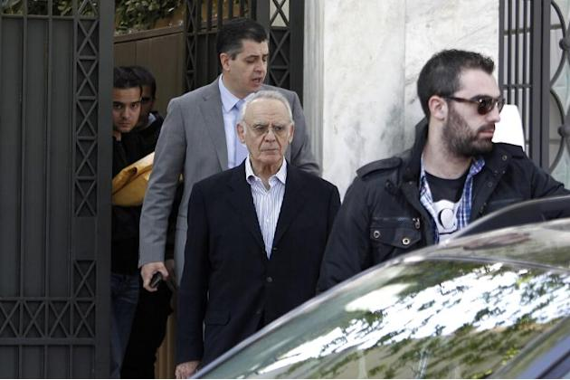 Former Greek minister Akis Tsochatzopoulos (C) is taken from his home in Athens on April 11, 2012 to a prosecutor by officials from the Finance Ministry's anti-fraud squad