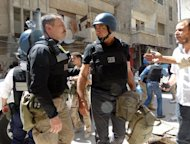 UN arms experts inspect a site suspected of being hit by chemical weapons in a Damascus suburb on August 28, 2013