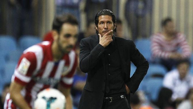 Atletico de Madrid's coach Diego Simeone from Argentina gestures during a Spanish La Liga soccer match against Osasuna at the Vicente Calderon stadium in Madrid, Spain, Tuesday, Sept. 24, 2013