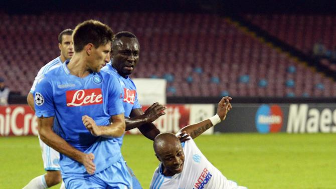 Marseille's Kassim Abdallah, right, kicks the ball past Napoli's Federico Fernandez, left, and Pablo Armero, during a Champions League, group F, soccer match between Napoli and Marseille, at the Naples San Paolo stadium, Italy, Wednesday, Nov. 6, 2013