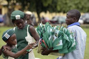 A vendor carries Nigerian national flags on October…