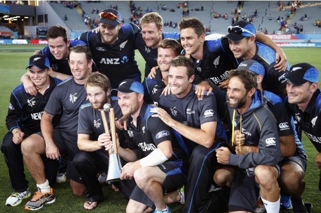 Members of the New Zealand team celebrate with the Chappell-Hadlee trophy after beating Australia in their Cricket World Cup match in Auckland
