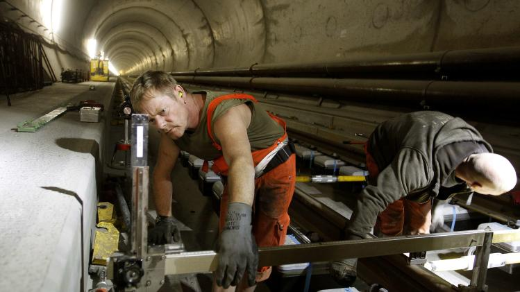 A worker uses a measuring gauge during the installation of the railway tracks in the NEAT Gotthard Base tunnel near Erstfeld
