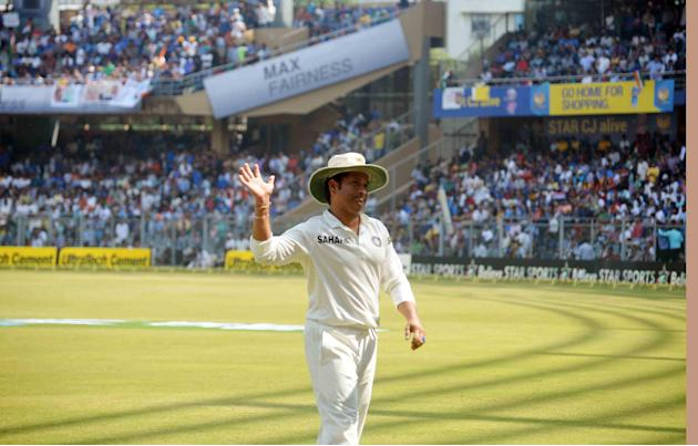 Cricket legend Sachin Tendulkar waves to the crowd at Wankhede stadium as he bids adieu to international cricket in Mumbai on Nov.16, 2013. (Photo: Sandeep Mahankal/IANS)