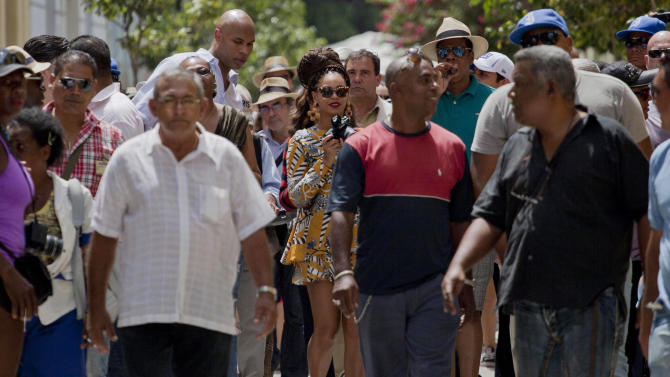 U.S. singer Beyonce, center holding camera, walks with her husband, rapper Jay-Z, right of her, as they tour Old Havana, Cuba, Thursday, April 4, 2013. R&B's power couple is in Havana on their fifth wedding anniversary. (AP Photo/Ramon Espinosa)