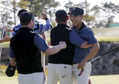 Bae of South Korea celebrates with teammates after sinking putt to defeat U.S.'s Fowler and Walker on 18th hole during four ball matches of 2015 Presidents Cup golf tournament in Incheon